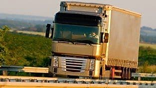 Truck driving on highway, green country background
